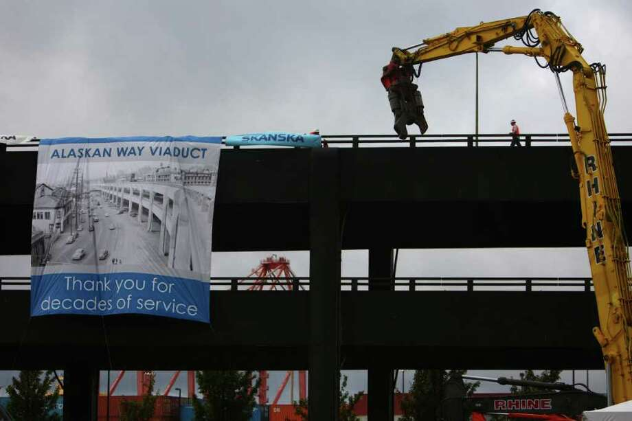 Workers hang a banner on the Alaskan Way Viaduct as he aging structure begins to come down on Saturday. Photo: JOSHUA TRUJILLO / SEATTLEPI.COM