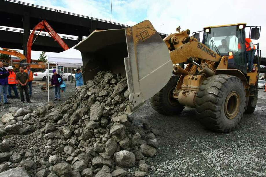 Governor Chris Gregoire operates a front-end-loader filled with rubble  from the Alaskan Way Viaduct during a celebration marking the beginning  of its demolition in downtown Seattle. Photo: JOSHUA TRUJILLO / SEATTLEPI.COM