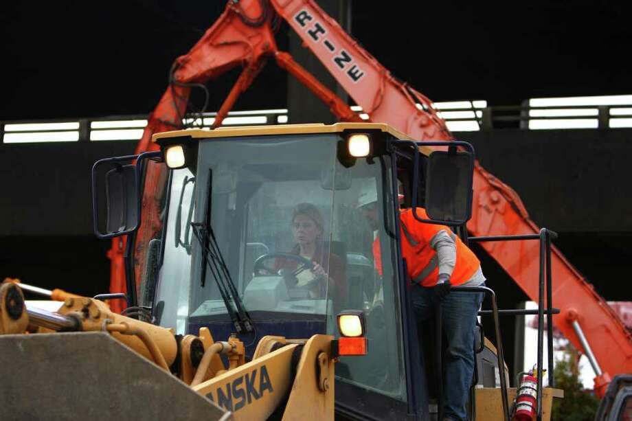 Governor Chris Gregoire operates a front-end-loader filled with rubble 