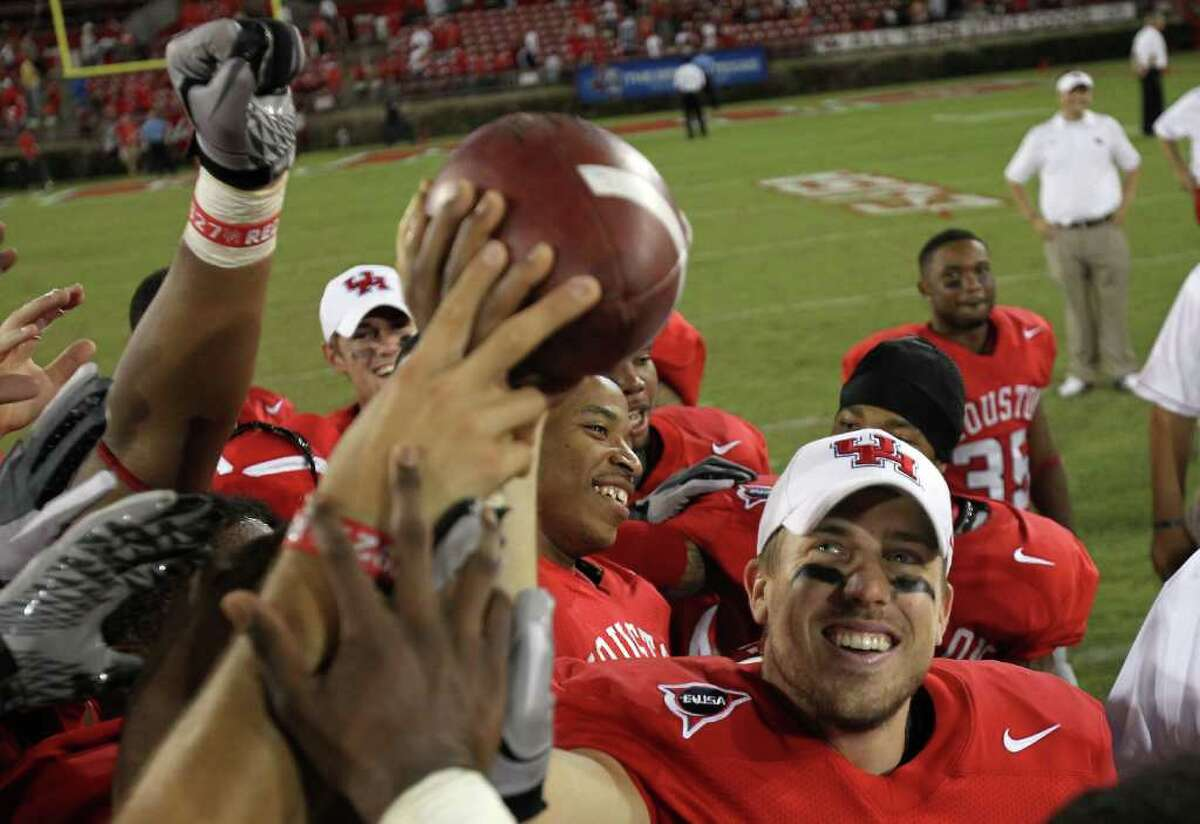 University of Houston quarterback Case Keenum (7) holds up a game ball he got for becoming the NCAA all time leader in total offense after winning a NCAA football game against Marshall University, Saturday, Oct. 22, 2011, at Robertson Stadium in Houston.