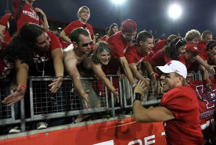 University of Houston quarterback Case Keenum (7) gives the student section a dose of high fives aft