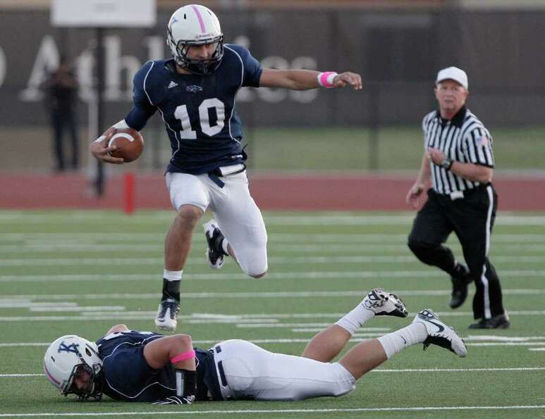 10/22/11: Running back  Alex Coogan #10 of the Kingwood Mustangs  hurdles his own player while rushi