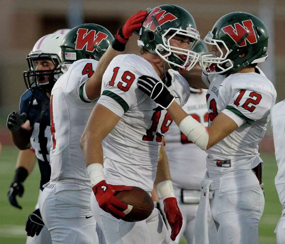 10/22/11: Wide receiver Jayme Taylor #19 is congratulated for a first down by Cameron Klapesky #12 of The Woodlands Highlanders  against the Kingwood Mustangs in a high school football game at Turner Stadium in Humble, Texas. For the Chronicle: Thomas B. Shea Photo: For The Chronicle: Thomas B. She