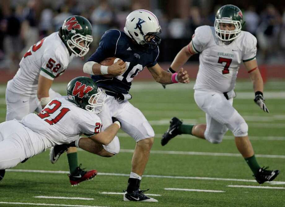 10/22/11: Running back  Alex Coogan #10 of the Kingwood Mustangs  breaks the tackle of linebacker Cole Little #21 of The Woodlands Highlanders in a high school football game at Turner Stadium in Humble, Texas. For the Chronicle: Thomas B. Shea Photo: For The Chronicle: Thomas B. She