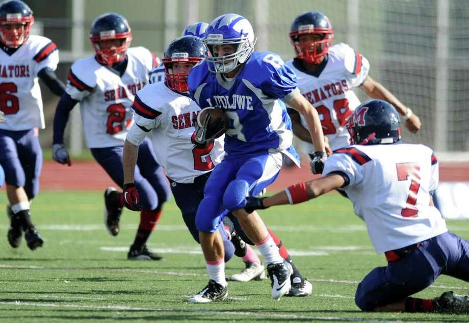 Fairfield Ludlowe's Danny Santella carries the ball through a pack of Brien McMahon defenders Saturday, Oct. 22, 2011 during their game at Taft Field in Fairfield, Conn. Photo: Autumn Driscoll / Connecticut Post