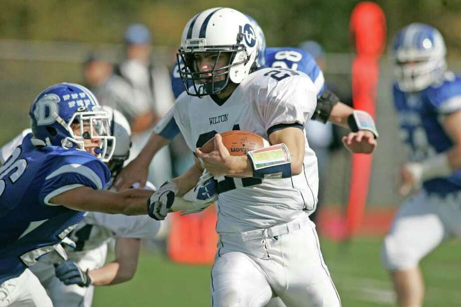 Wilton RB Travis Stella rips off 1 39 yard run on the first play off scrimmage during an FCIAC battle betweem Wilton and Darien.