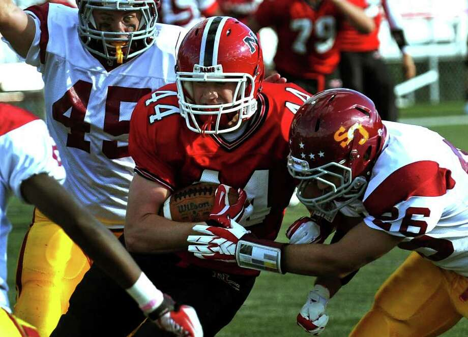 Highlights from boys football action between New Canaan and St. Joseph in New Canaan, Conn. on Saturday October 22, 2011. New Canaan's #44 Connor Kilbane is tackled by St. Joseph's #26 EJ Sheehan, right. Photo: Christian Abraham / Connecticut Post