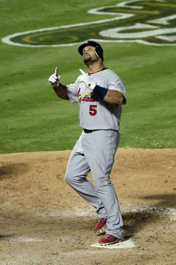 ARLINGTON, TX - OCTOBER 22:  Albert Pujols #5 of the St. Louis Cardinals celebrates after hitting a solo home run in the ninth inning for his third home run of the night during Game Three of the MLB World Series against the Texas Rangers at Rangers Ballpark in Arlington on October 22, 2011 in Arlington, Texas. The Cardinals won 16-7. Photo: Ezra Shaw, Getty / 2011 Getty Images