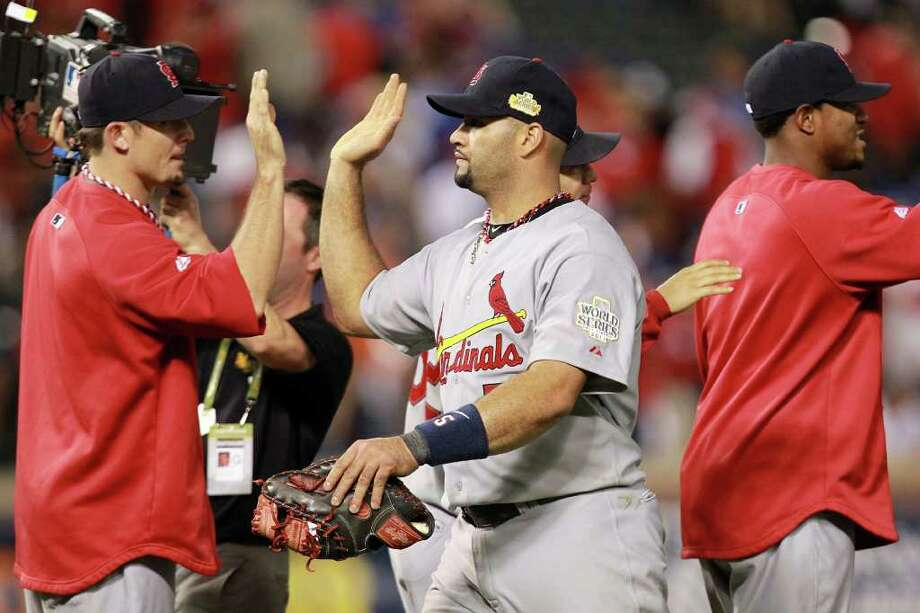 ARLINGTON, TX - OCTOBER 22:  Albert Pujols #5 of the St. Louis Cardinals celebrates with teammates after defeating the Texas Rangers 16-7 in Game Three of the MLB World Series at Rangers Ballpark in Arlington on October 22, 2011 in Arlington, Texas. Photo: Ronald Martinez, Getty / 2011 Getty Images