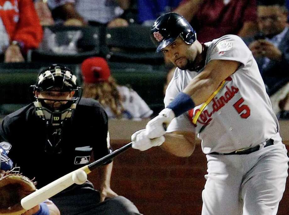 Game 3: Cardinals 16, Rangers 7 (Cardinals lead series 2-1). St. Louis Cardinals' Albert Pujols hits a solo home run during the ninth inning of Saturday's game in Arlington. Pujols tied a World Series single-game record with three homers. Photo: Eric Gay, Associated Press / AP