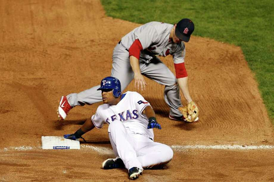 ARLINGTON, TX - OCTOBER 22: Adrian Beltre #29 of the Texas Rangers is safe at third base after the tag by Ryan Theriot #3 of the St. Louis Cardinals in the seventh inning during Game Three of the MLB World Series at Rangers Ballpark in Arlington on October 22, 2011 in Arlington, Texas. Photo: Tom Pennington, Getty / 2011 Getty Images