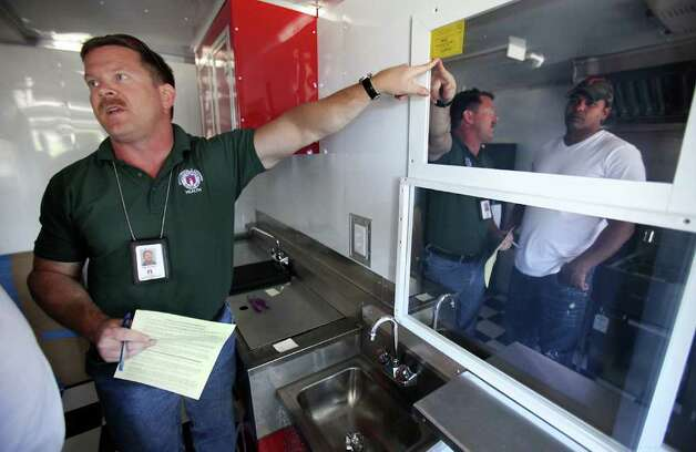 Jeff Walters, left, Sanitarian Senior inspector for the City of Austin, points out the expiration date on the license to operate, to Daniel Brown, right, owner of the Daniel Brown's Bar B Que food trailer.  Mobile food vendors in Austin flourish in the downtown area as well as the outskirts of the business center Tuesday, Oct. 18, 2011.  The city of San Antonio is discussing the possibility of loosening up mobile vendor restrictions. Photo: BOB OWEN, Bob Owen/rowen@express-news.net / rowen@express-news.net