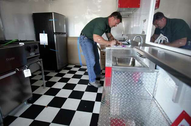 Jeff Walters, Sanitarian Senior inspector for the City of Austin, fills out forms as he inspects a mobile food trailer owned by Daniel Brown.  Mobile food vendors in Austin flourish in the downtown area as well as the outskirts of the business center Tuesday, Oct. 18, 2011.  The city of San Antonio is discussing the possibility of loosening up mobile vendor restrictions. Photo: BOB OWEN, Bob Owen/rowen@express-news.net / rowen@express-news.net