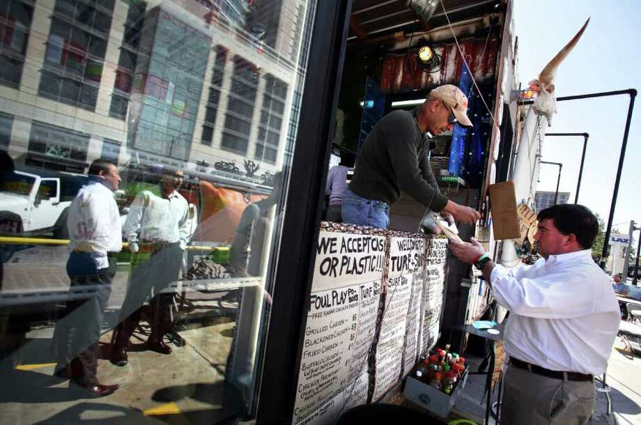 Lalo Reyes, second from right, takes an order from Bryan Poe, right, at the Turf and Surf Po-Boys food trailer near the corner of 2nd St. and Congress in Austin.  Mobile food vendors in Austin flourish in the downtown area as well as the outskirts of the business center Tuesday, Oct. 18, 2011.  The city of San Antonio is discussing the possibility of loosening up mobile vendor restrictions. Photo: BOB OWEN, Bob Owen/rowen@express-news.net / rowen@express-news.net