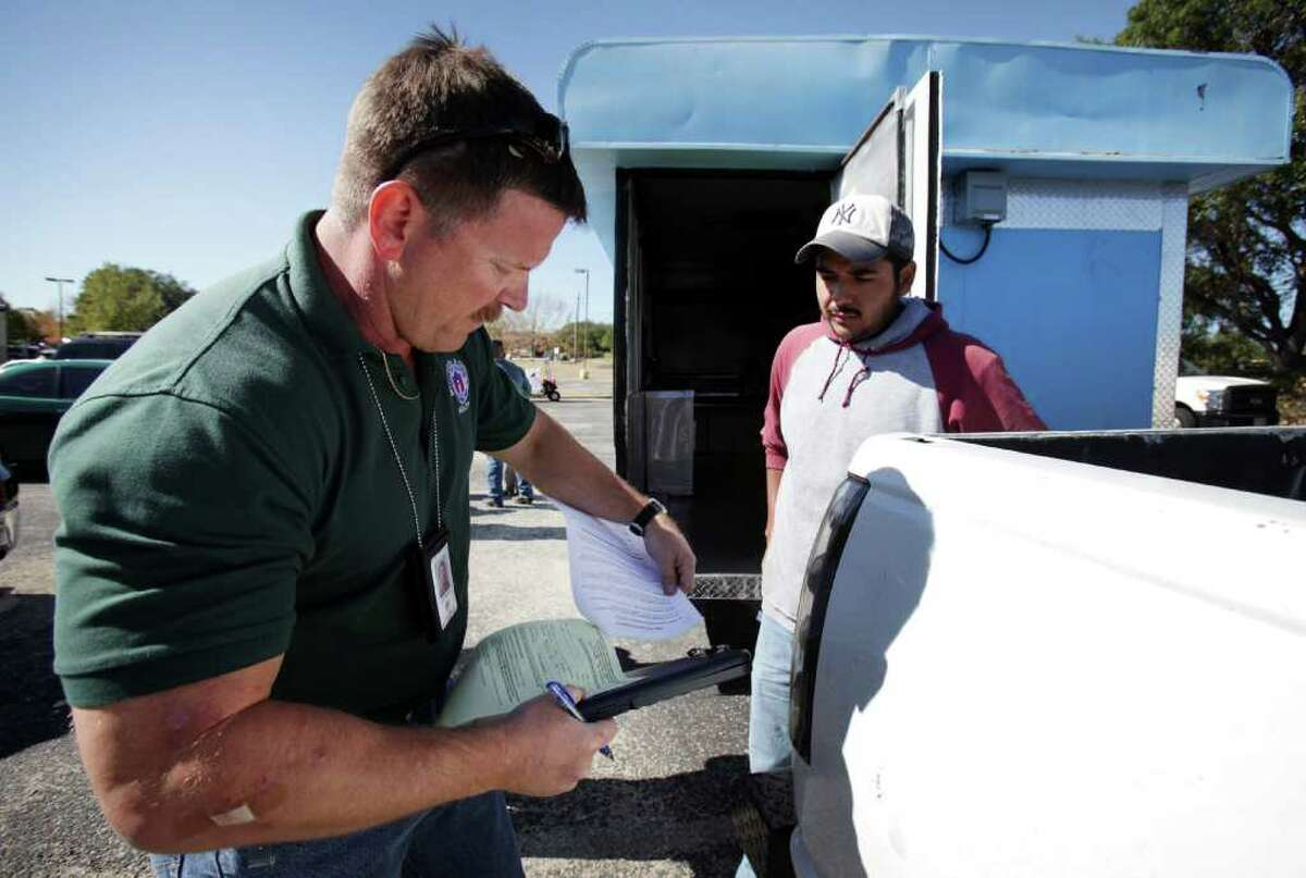 Jeff Walters, Sanitarian Senior inspector for the City of Austin, tears off a copy showing the repairs Christian Olarte, right, needs to make to his mobile food vending unit before he can get his license to operate. Mobile food vendors in Austin flourish in the downtown area as well as the outskirts of the business center Tuesday, Oct. 18, 2011. The city of San Antonio is discussing the possibility of loosening up mobile vendor restrictions.