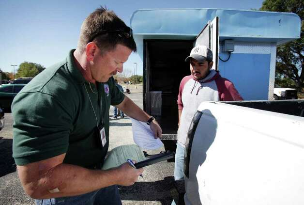 Jeff Walters, Sanitarian Senior inspector for the City of Austin, tears off a copy showing the repairs Christian Olarte, right, needs to make to his mobile food vending unit before he can get his license to operate.  Mobile food vendors in Austin flourish in the downtown area as well as the outskirts of the business center Tuesday, Oct. 18, 2011.  The city of San Antonio is discussing the possibility of loosening up mobile vendor restrictions. Photo: BOB OWEN, Bob Owen/rowen@express-news.net / rowen@express-news.net