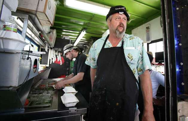 Ralph Gilmore, owner of Turf and Surf Po-Boys food trailer serves tacos and po-boys from his downtown Austin location.  Mobile food vendors in Austin flourish in the downtown area as well as the outskirts of the business center Tuesday, Oct. 18, 2011.  The city of San Antonio is discussing the possibility of loosening up mobile vendor restrictions. Photo: BOB OWEN, Bob Owen/rowen@express-news.net / rowen@express-news.net