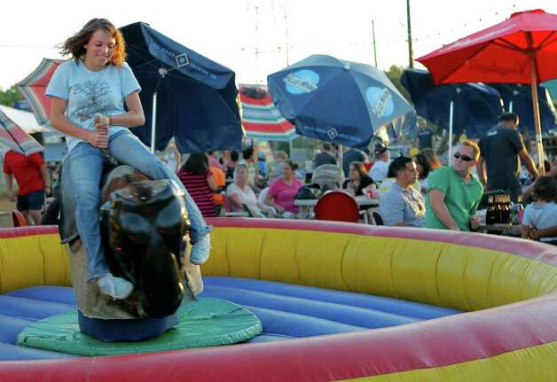 Audrie Abdallah rides a mechanical bull during Boardwalk on Bulverde at Bulverde Road on Saturday, Oct. 1, 2011. Photo: MICHAEL MILLER, Express-News / mmiller@express-news.net