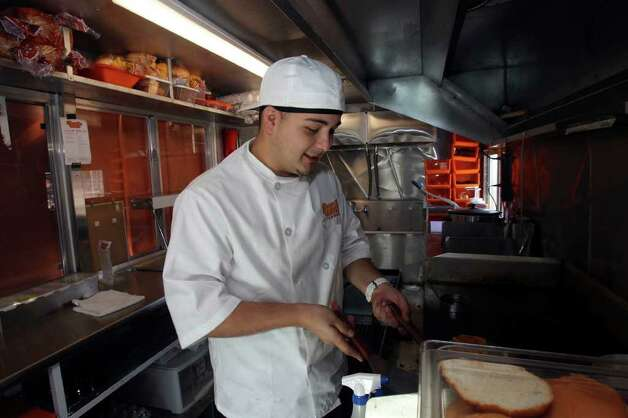 Dominic Chacon cooks a burger in his Toastie Buns food truck at the Boardwalk on Bulverde Wednesday January 19, 2011. Chacon is a culinary student at St. Philip's College and hopes to have a career in the restaurant industry. Photo: JOHN DAVENPORT, Express-News / jdavenport@express-news.net