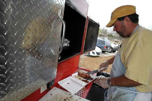 Keith Hill, owner of K. Hill BBQ Company, serves up a plate fresh from the smoker. Photo: JENNIFER WHITNEY, Express-News / special to the Express-News