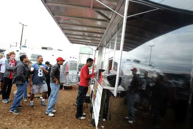 Customers wait in line to sample the goods at K. Hill BBQ Company during the grand opening of Boardwalk on Bulverde, San Antonio's first mobile food truck park, Saturday, January 8, 2011. Photo: JENNIFER WHITNEY, Express-News / special to the Express-News