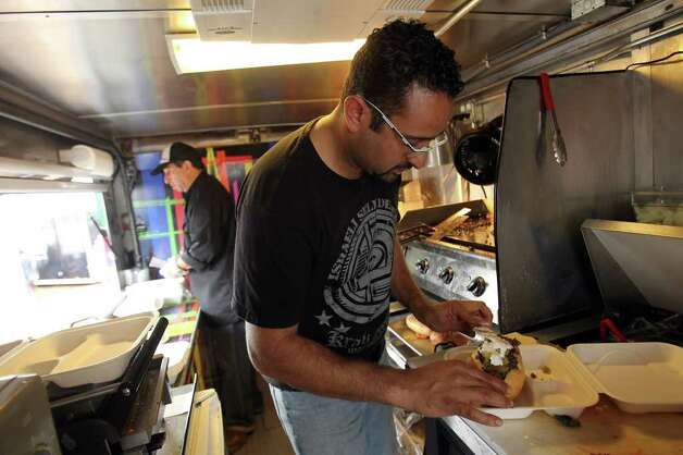 Neil Hajji, owner of Wheelie Gourmet, plates a sandwich during the grand opening of Boardwalk on Bulverde, San Antonio's first mobile food truck park, Saturday, January 8, 2011. Photo: JENNIFER WHITNEY, Express-News / special to the Express-News