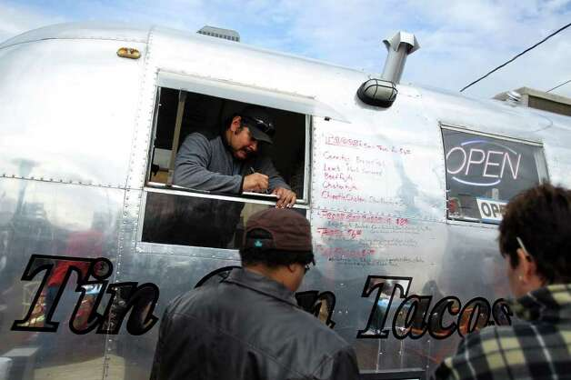 German Teran takes customer orders through the window of Tin Can Tacos' Airstream during the grand opening of Boardwalk on Bulverde, San Antonio's first mobile food truck park, Saturday, January 8, 2011. Photo: JENNIFER WHITNEY, Express-News / special to the Express-News