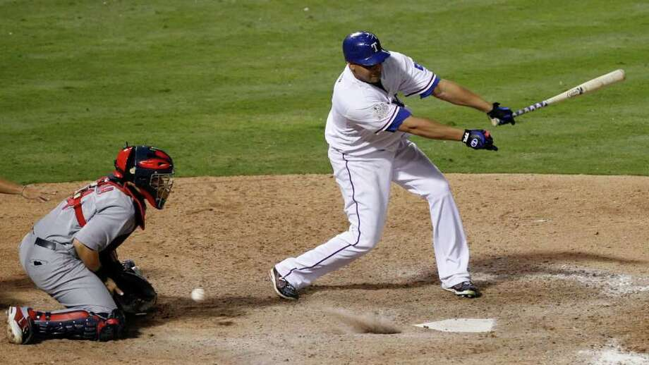 Texas Rangers' Nelson Cruz strikes out to end the game in front of St. Louis Cardinals catcher Yadier Molina, left, in Game 3 of the World Series at Rangers Ballpark in Arlington on Saturday, October 22, 2011, in Arlington, Texas. The Cardinals took a 2-1 series lead with a 16-7 victory. (Ron T. Ennis/Fort Worth Star-Telegram/MCT) Photo: Ron T. Ennis / Fort Worth Star-Telegram