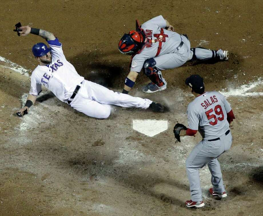 St. Louis Cardinals catcher Yadier Molina tags out Texas Rangers' Mike Napoli after trying to score on a sacrifice fly by Yorvit Torrealba during the fourth inning of Game 3 of baseball's World Series Saturday, Oct. 22, 2011, in Arlington, Texas. (AP Photo/Matt Slocum) Photo: Matt Slocum / AP