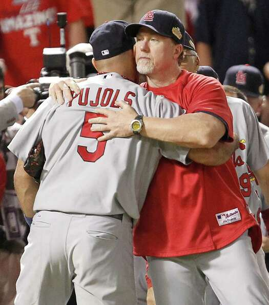 St. Louis Cardinals' Albert Pujols (5) is greeted byCardinals batting coach Mark McGwire after a 16-