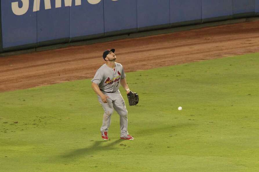 St. Louis Cardinals left fielder Matt Holliday watches a fly ball come down as a ball thrown by a fa