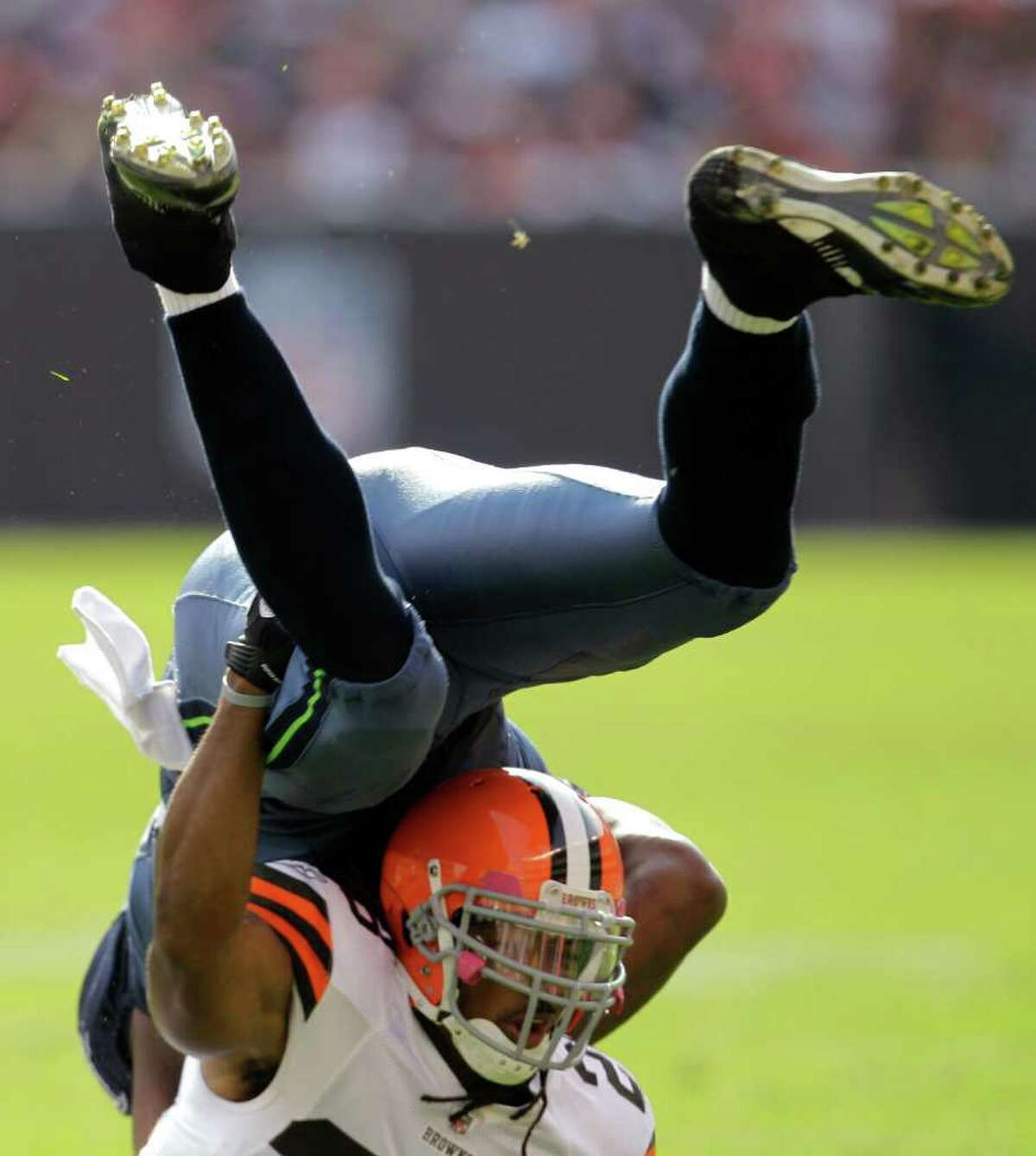 Cleveland Browns safety Usama Young, bottom, flips Seattle Seahawks tight end Anthony McCoy after a 3-yard pass in the third quarter of an NFL football game Sunday, Oct. 23, 2011, in Cleveland.