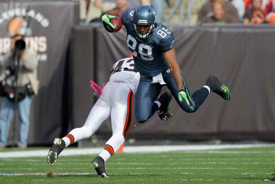 Seattle Seahawks tight end Cameron Morrah (88) sails over Cleveland Browns safety T.J. Ward  after a