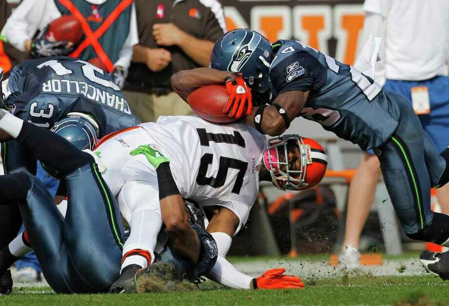 Cleveland Browns wide receiver Greg Little (15) is hit by Seattle Seahawks cornerback Walter Thurmond, right, and strong safety Kam Chancellor (31) after a catch in the second quarter of an NFL football game Sunday, Oct. 23, 2011, in Cleveland. Photo: AP
