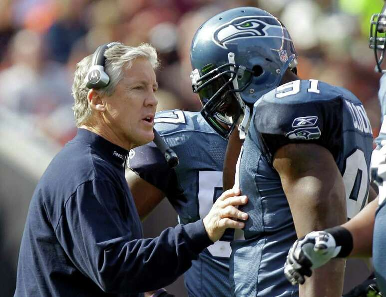 Seattle Seahawks head coach Pete Carroll talks to defensive end Chris Clemons (91) during a time out