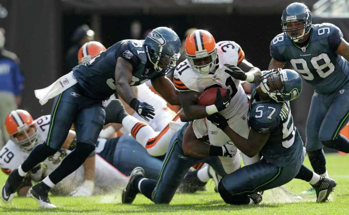 Cleveland Browns' Montario Hardesty runs the ball for 6 yards against the Seattle Seahawks in the third quarter in an NFL football game Sunday, Oct. 23, 2011, in Cleveland. Seahawks strong safety Kam Chancellor (31) and linebacker David Hawthorne defend.