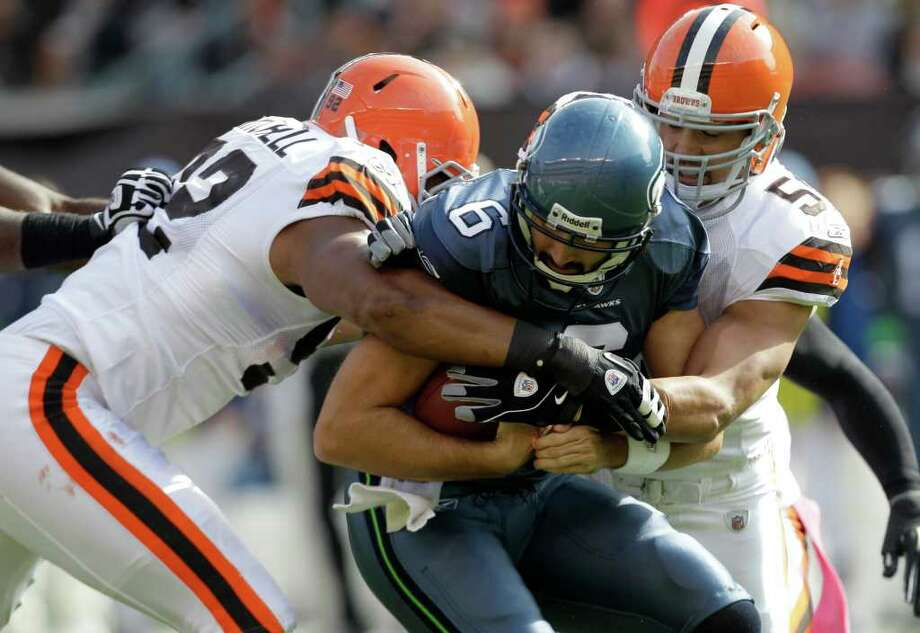 Seattle Seahawks quarterback Charlie Whitehurst (6) is sacked by Cleveland Browns defensive end Jayme Mitchell, left, and linebacker Chris Gocong in the first quarter of an NFL football game Sunday, Oct. 23, 2011, in Cleveland. Photo: AP