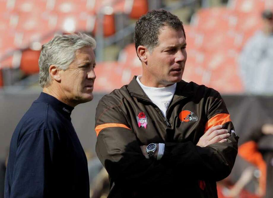 Seattle Seahawks head coach Pete Carroll, left, and Cleveland Browns head coach Pat Shurmur watch their teams warm up before an NFL football game Sunday, Oct. 23, 2011, in Cleveland. Photo: AP