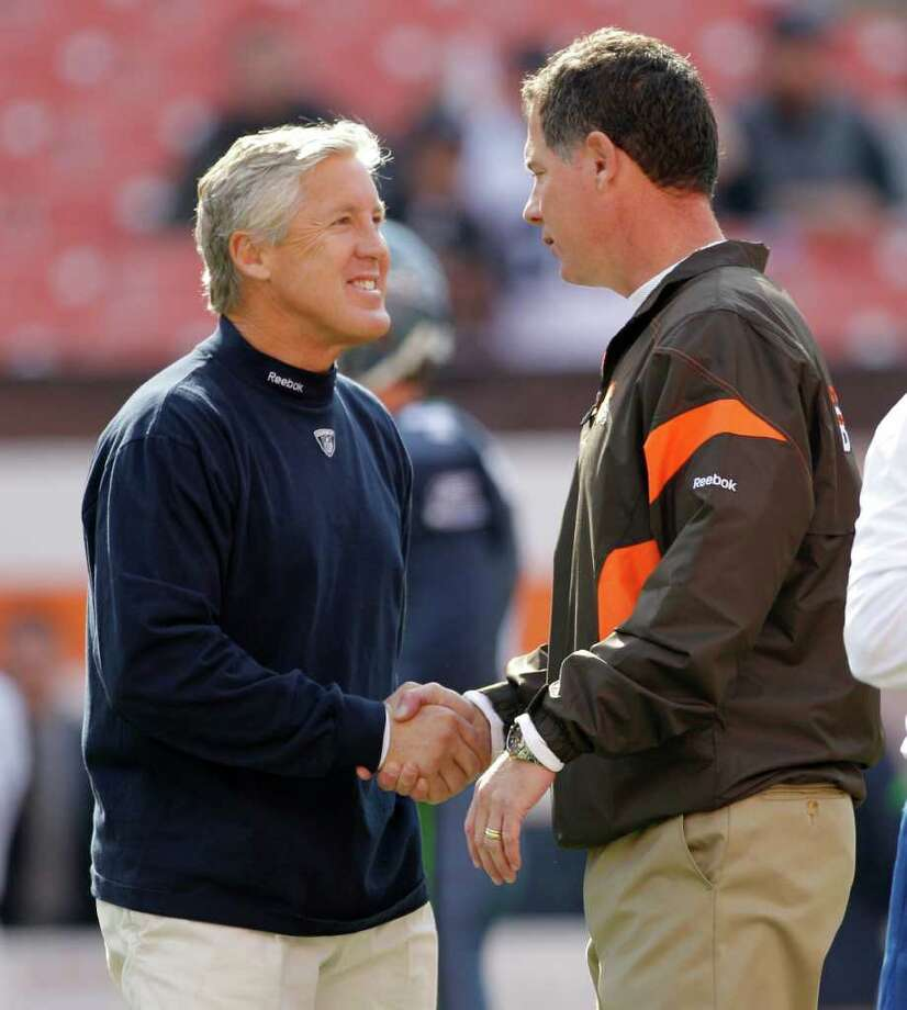 Seattle Seahawks head coach Pete Carroll, left, greets Cleveland Browns head coach Pat Shurmur before the start of an NFL football game on Sunday, Oct. 23, 2011, in Cleveland. Photo: AP