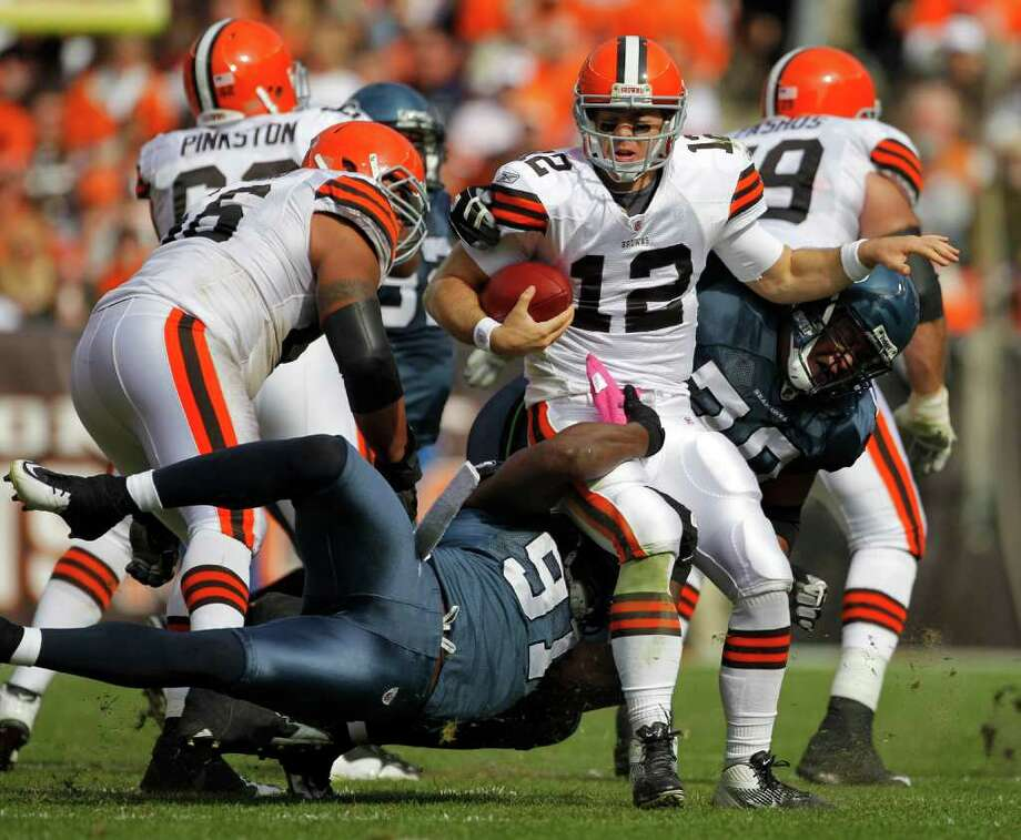 Cleveland Browns quarterback Colt McCoy (12) is sacked by Seattle Seahawks defensive ends Chris Clemons (91) and Red Bryant, right, in the second quarter of an NFL football game Sunday, Oct. 23, 2011, in Cleveland. Photo: AP