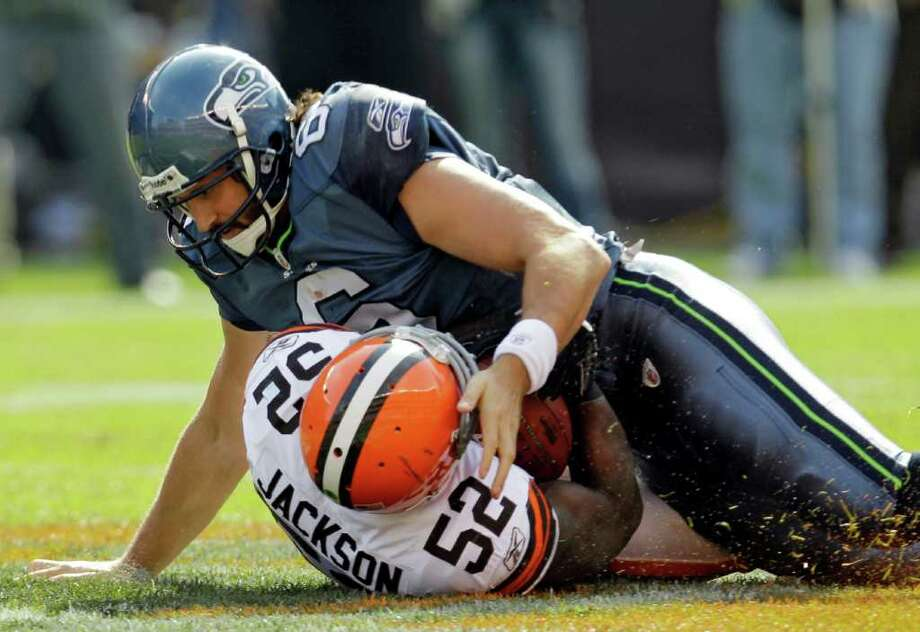 Seattle Seahawks quarterback Charlie Whitehurst lands on Cleveland Browns linebacker D'Qwell Jackson (52) after Jackson recovered a fumble by Whitehurst in the second quarter of an NFL football game Sunday, Oct. 23, 2011, in Cleveland. Photo: AP