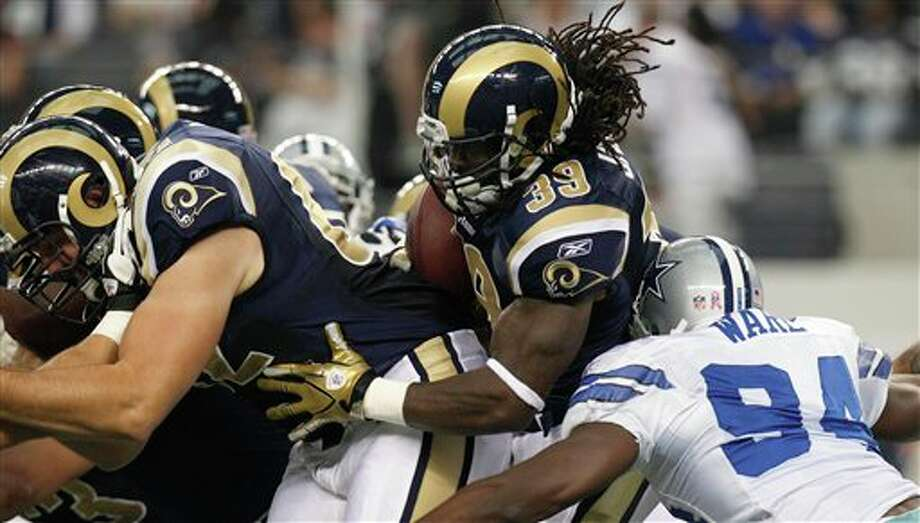 St. Louis Rams running back Steven Jackson (39) tries to find an opening behind teammate Harvey Dahl (62) as Dallas Cowboys outside linebacker DeMarcus Ware (94) grabs hold during the first half of the NFL football game at Cowboys Stadium in Arlington, Texas, Sunday, Oct. 23, 2011.  (AP Photo/LM Otero) Photo: LM Otero, Associated Press / AP