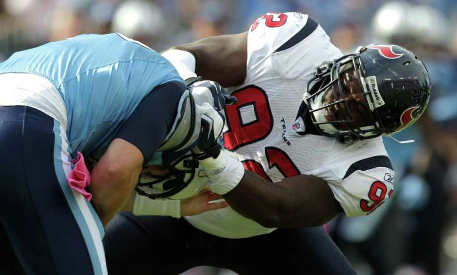 Houston Texans defensive tackle Earl Mitchell (92) grabs Tennessee Titans quarterback Jake Locker (10) in the backfield during the fourth quarter of an NFL football game at LP Field Sunday, Oct. 23, 2011, in Nashville. The Texans beat the Titans 41-7. Photo: Brett Coomer, Houston Chronicle / © 2011  Houston Chronicle