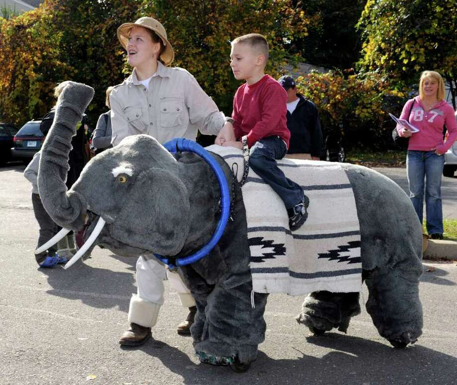 Grant Plourde, 4, gets a ride on a huge stuffed elephant led around by Mallory Foster, 16. The rides were available at the Danbury Kids Fest held at the Danbury PAL building Sunday. 100% of all proceeds from ticket sales go to the American Cancer Society. Photo taken Sunday, Oct. 23, 2011. Photo: Carol Kaliff / The News-Times