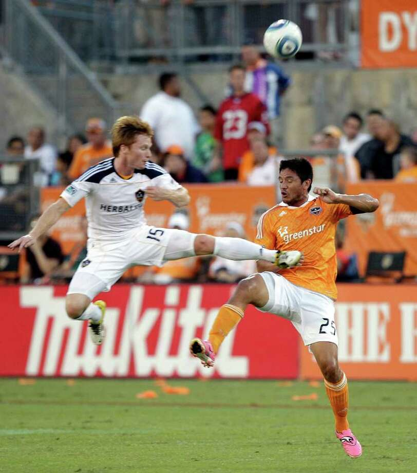 HOUSTON - OCTOBER 23:  Dan Keat #15 of the Los Angeles Galaxy catches Brian Ching #25 of the Houston Dynamo with a high foot as they battle for the ball at Robertson Stadium on October 23, 2011 in Houston, Texas. Photo: Bob Levey, Getty / 2011 Getty Images