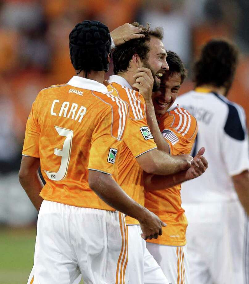 Adam Moffat #16 (C) of the Houston Dynamo is congratulated by Danny Cruz #5 (R) and Calen Carr #3 after scoring against the Los Angeles Galaxy in the first half at Robertson Stadium on October 23, 2011 in Houston, Texas. Photo: Bob Levey, Getty / 2011 Getty Images