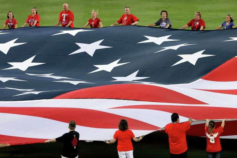 ARLINGTON, TX - OCTOBER 23:  An American flag is held during the performance of the Star Spangled Banner prior to Game Four of the MLB World Series between the St. Louis Cardinals and the Texas Rangers at Rangers Ballpark in Arlington on October 23, 2011 in Arlington, Texas. Photo: Doug Pensinger, Getty / 2011 Getty Images