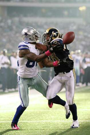 Under pressure from St. Louis Rams corner back Josh Gordy, Dallas Cowboys wide receiver Dez Bryant pulls in a pass from Tony Romo for a fourth quarter touchdown at Cowboys Stadium in Arlington, Texas, Sunday, Oct. 23, 2011.  JERRY LARA/glara@express-news.net Photo: JERRY LARA, Express-News / SAN ANTONIO EXPRESS-NEWS