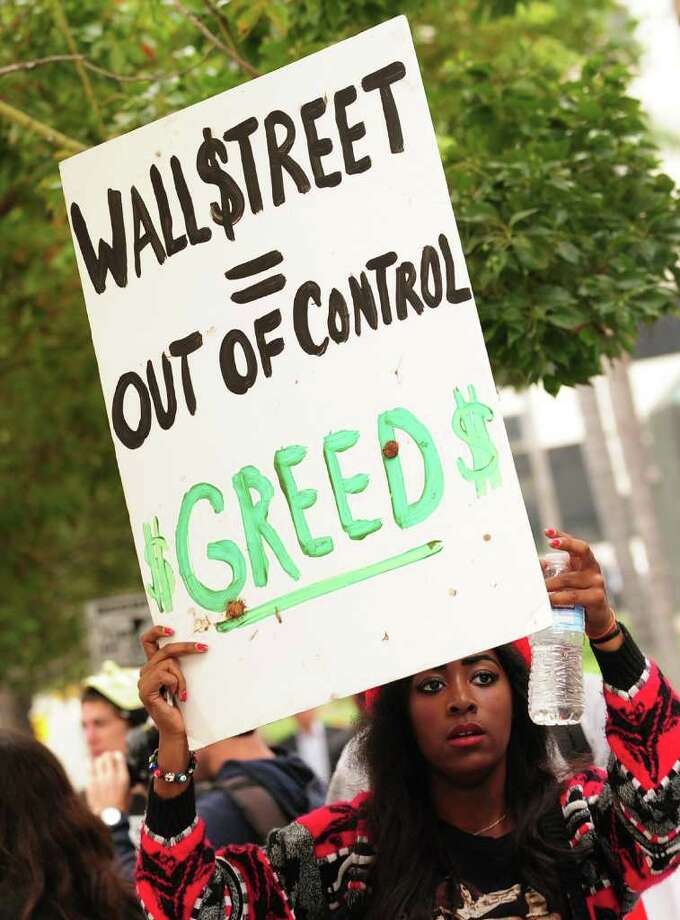 A woman holds a placard equating Wall Street with greed as a small group of protesters march past banks in downtown Los Angeles on October 19, 2011. Calling themselves members of the 99 percent and demanding a world that works through democracy and not corporatocracy, the demonstrators have been camped out in front of their base at City Hall in solidarity with the Occupy Wall Street movement, as a symbolic gesture of discontent over the current economic and political climate. AFP PHOTO / Frederic J. BROWN (Photo credit should read FREDERIC J. BROWN/AFP/Getty Images) Photo: FREDERIC J. BROWN / AFP