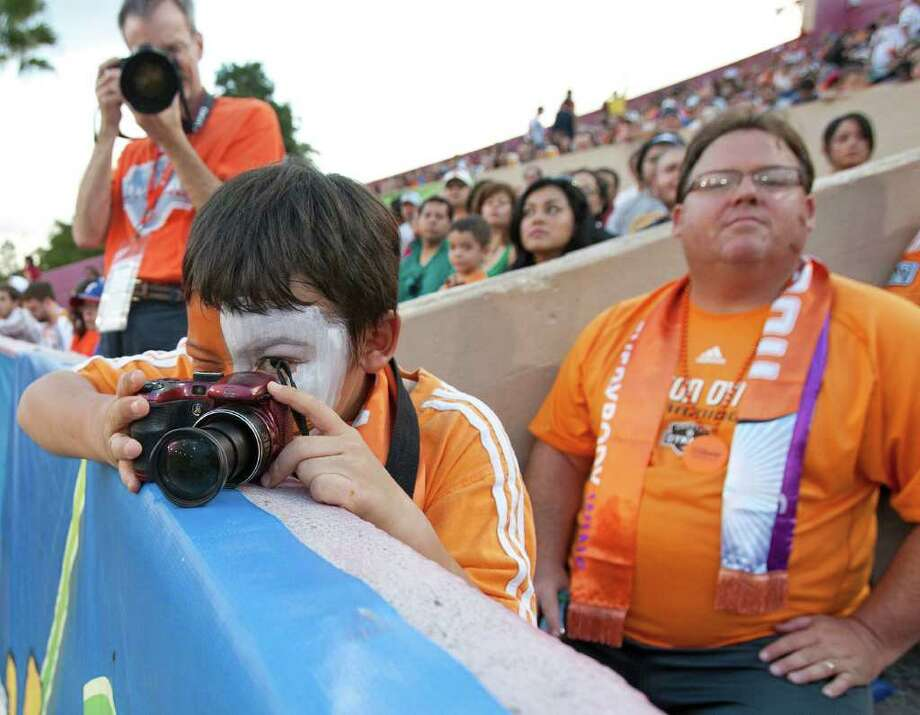 Eight-year-old Christopher Jerrells left, looks through his camera as his father Michael Jerrells looks on as the Houston Dynamo play the LA Galaxy during the first period in MLS game action at Robertson Stadium Sunday, Oct. 23, 2011, in Houston. Photo: James Nielsen, Chronicle / © 2011 Houston Chronicle